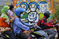 Motorists ride past a mural honoring health care workers during the new coronavirus outbreak in Jakarta, Indonesia.