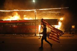 A protester carries the carries a U.S. flag upside, a sign of distress, next to a burning building Thursday, May 28, 2020, in Minneapolis.
