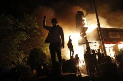 Protesters gather in front of a burning fast food restaurant Friday, May 29, 2020, in Minneapolis.