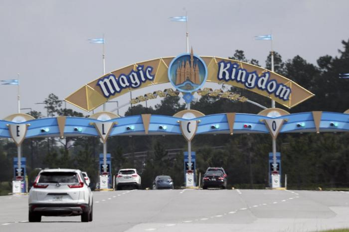 Park guests enter the Magic Kingdom during the reopening of Walt Disney World Saturday, July 11, 2020, in Lake Buena Vista, Fla.