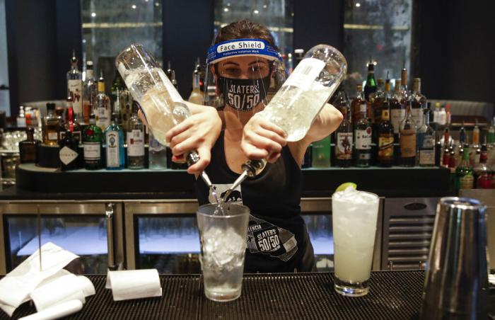 A bartender mixes a drink while wearing a mask and face shield at Slater's 50/50 in Santa Clarita, Calif.