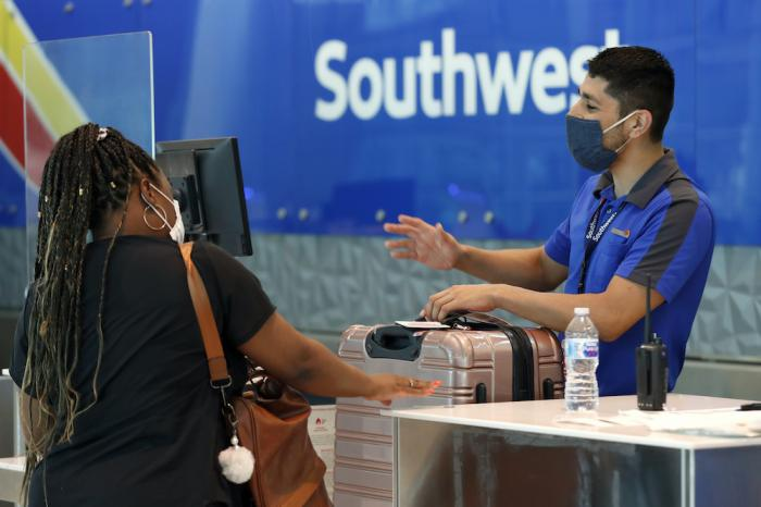 Southwest airlines employee Oscar Gonzalez, right, assists a passenger at the ticket counter at Love Field in Dallas.