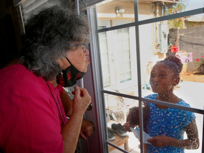"Zita Robinson, left, who's 77 and diabetic, blows a kiss to her granddaughter Traris ""Trary"" Robinson-Newman, 8, who blows a kiss back to her, Tuesday, Aug. 4, 2020, in Phoenix"