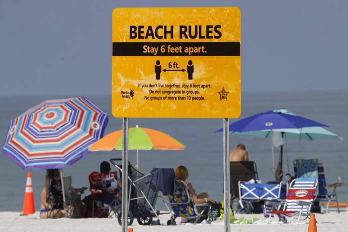 Visitors sunbathe after the beach officially reopened to the public in Clearwater Beach, Fla.,