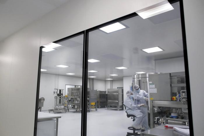 Laboratory technicians work at the mAbxience biopharmaceutical company on an experimental coronavirus vaccine developed by Oxford University and the laboratory AstraZeneca.