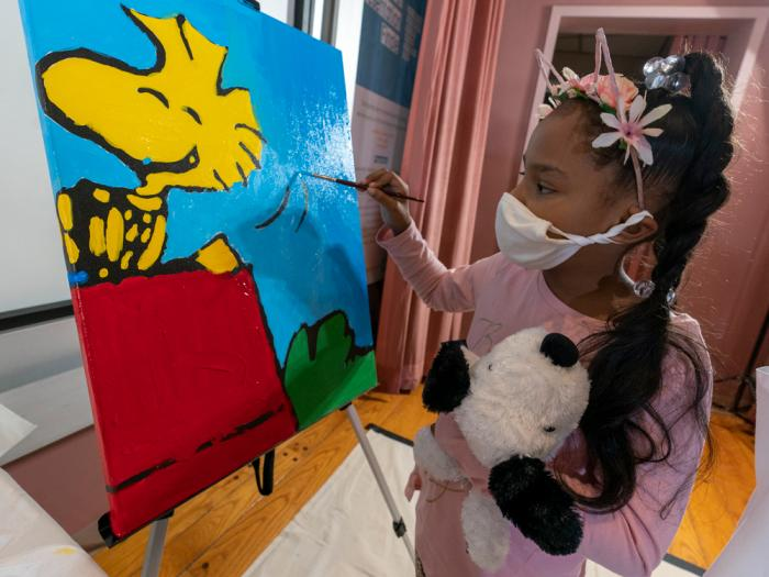 "Kaley Williams, 8, paints a panel of a ""Peanuts"" mural that will be placed in the outpatient pediatric floor of One Brooklyn Health at Brookdale Hospital, Thursday, Oct. 1, 2020, in the Brooklyn borough of New York"