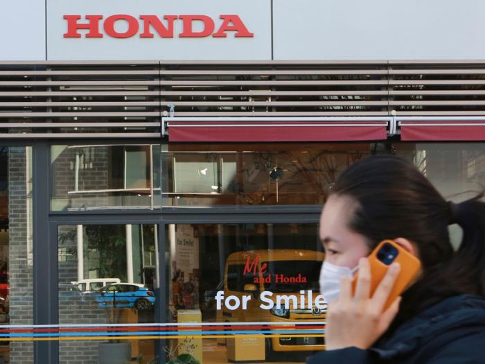 A woman wearing a face mask walks in front of a Honda Motor Co. showroom in Tokyo, Tuesday, Feb. 9, 2021