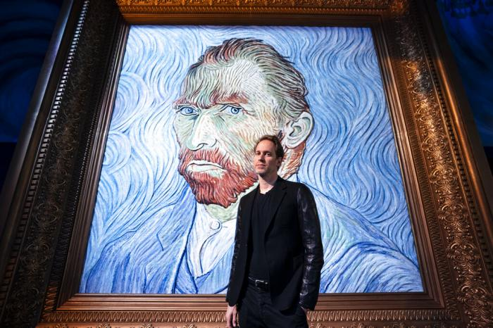 David Korins stands beside a giant replica of celebrated painter Vincent Van Gogh's self portrait at a preview of the Immersive Van Gogh exhibit at Pier 36.
