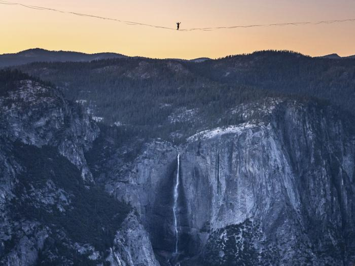 In this Saturday, June 12, 2021, photo provided by Scott Oller Films, highliner Daniel Monterrubio walks the 2,800-foot-long line off Taft Point above Yosemite Valley in Yosemite, Calif.
