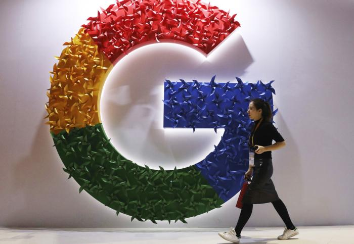In this Monday, Nov. 5, 2018 file photo, a woman walks past the logo for Google at the China International Import Expo in Shanghai