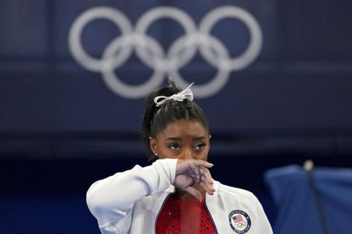 Simone Biles, of the United States, watches gymnasts perform at the 2020 Summer Olympics, Tuesday, July 27, 2021,