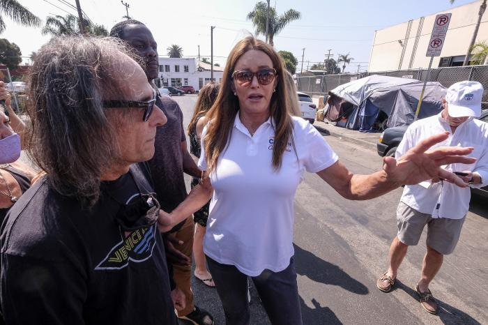 Caitlyn Jenner, center, a Republican candidate for California governor, talks with Patrick Liberty, left, prior to a news conference in the Venice Beach section of Los Angeles, Thursday, Aug. 12, 2021.