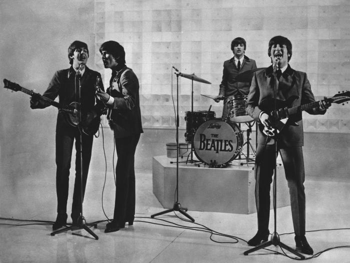 The Beatles are seen performing, date unknown. From left to right: Paul McCartney, George Harrison, Ringo Starr, and John Lennon.